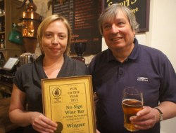 Becky Oliver, licensee of the No Sign Bar, receives the Swansea Camra Pub of the Year award from branch chairman Colin Smith.
