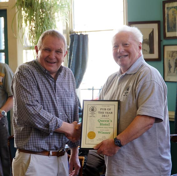 Gary Owen, landlord of The Queen's Hotel, receives the Swansea Camra Pub of the Year award from chairman Paul James, right.